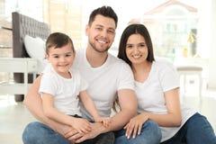 Gelukkige ouders en hun zoonszitting samen op vloer Familietijd stock foto
