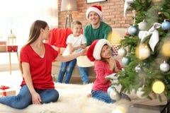 Gelukkige ouders en kinderen die Kerstboom verfraaien Royalty-vrije Stock Foto