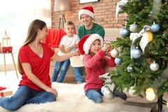 Gelukkige ouders en kinderen die Kerstboom verfraaien Stock Afbeelding