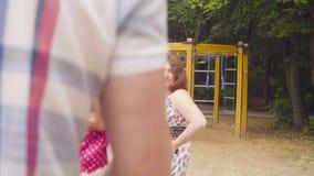 Gelukkige ouders met babymeisje het slingeren op een schommeling stock video