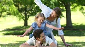 Gelukkige ouders met hun meisje in het park stock footage