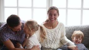 Gelukkige ouders met jonge geitjes die pret het lachen het kietelen op bank hebben stock videobeelden