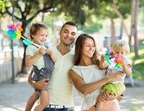 Gelukkige ouders met kinderen die windmolens spelen Royalty-vrije Stock Foto's