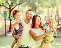 Gelukkige ouders met kinderen die windmolens spelen Royalty-vrije Stock Foto