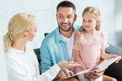 gelukkige ouders met leuk weinig boek van de dochterlezing samen stock afbeeldingen