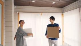 Gelukkige paar brengende dozen met persoonlijke dingen na verhuizing aan nieuw huis, rond het kijken, het glimlachen en het kusse stock videobeelden