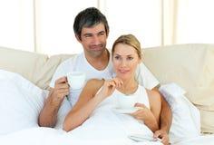 Gelukkige paar het drinken koffie die in het bed ligt Stock Afbeeldingen