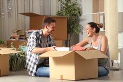 Gelukkige paar het lachen unboxing bezittingen die huis bewegen royalty-vrije stock afbeeldingen