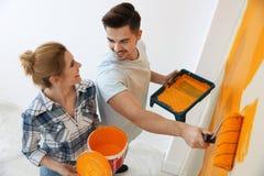 Gelukkige paar het schilderen muur binnen Huisreparatie stock foto's