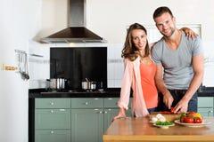 Gelukkige Paar Scherpe Groenten bij Keukenteller stock afbeeldingen