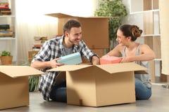 Gelukkige paar unboxing bezittingen die huis bewegen stock afbeelding