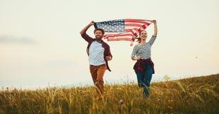 Gelukkige paarman en vrouw met vlag van Verenigde Staten die van de zonsondergang op aard genieten stock foto