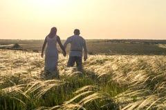Gelukkige paarman en vrouw in nationale Slavische kleren die op gebied op zonsondergang lopen en handen houden Onthaal aan Ruslan stock foto's