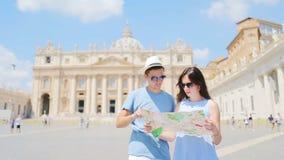 Gelukkige paartoeristen met kaart achtergrondst Peter Basiliekkerk in de stad van Vatikaan, Rome, Italië stock video