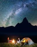Gelukkige paarwandelaars die dichtbij kampvuur en aanstekende tent onder ongelooflijk mooie sterrige hemel zitten Laag licht stock fotografie