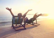 Gelukkige paarzitting bij zonstoelen op het strand van Koh Samet bij Stock Foto's