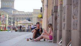 Gelukkige paarzitting in de straat op skateboard stock footage