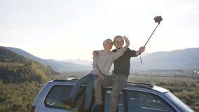 Gelukkige paarzitting op dak van auto en het possing op de smartphonecamera in de berg stock videobeelden