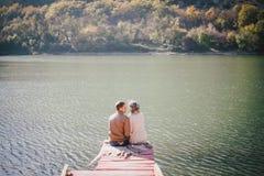 Gelukkige paarzitting op een houten brug dichtbij meer Stock Fotografie