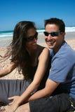 Gelukkige paarzitting op het strand royalty-vrije stock afbeeldingen