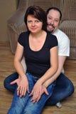 Gelukkige paarzitting op houten vloer stock foto