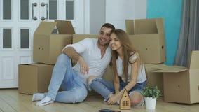 Gelukkige paarzitting op vloer in nieuw huis De jonge mens geeft sleutels aan zijn meisje en het kussen van haar stock videobeelden