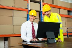 Gelukkige Pakhuisarbeider en Manager Using Computer royalty-vrije stock foto
