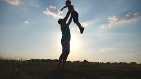 Gelukkige papa die op zijn kleine jongen werpen Vader en zoons het spelen op het gebied bij zonsondergang Papa en kind die pret h stock footage