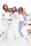 Gelukkige partijmeisjes die op laag springen Stock Afbeelding