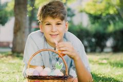 Gelukkige Pasen! De leuke glimlachende jongenstiener in blauw overhemd houdt mand met met de hand gemaakte gekleurde eieren op gr stock fotografie