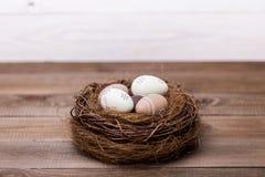 Gelukkige Pasen! De mooie paaseieren zijn verfraaid in bedkleuren in een nest op een houten achtergrond Conceptuele Pasen royalty-vrije stock fotografie