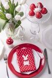Gelukkige Pasen Decor en lijst het plaatsen van de Pasen-lijst is een vaas met witte tulpen en schotels van rode en witte kleur P royalty-vrije stock foto