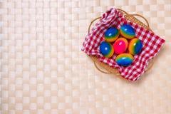 Gelukkige Pasen-decoratieachtergrond Hoogste mening van kleurrijke paaseieren in een mand op geruit servet op een licht beige taf royalty-vrije stock afbeeldingen