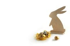 Gelukkige Pasen Een houten konijn en kwartelseieren, een gouden ei Gouden nest en gouden ei Kleine eieren stock foto's