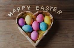 Gelukkige Pasen - gekleurde eieren in een hart gevormde kom Stock Fotografie