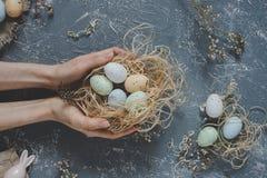 Gelukkige Pasen Handen die paaseieren in nest met Pasen-decoratie, hoogste mening houden Stock Foto's