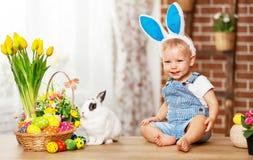 Gelukkige Pasen! het gelukkige grappige babyjongen spelen met konijntje stock fotografie