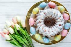 Gelukkige Pasen! Het gouden dienblad met plaat met cake en hand schilderde kleurrijke eieren, tulpen op witte houten lijst Sluit  stock fotografie
