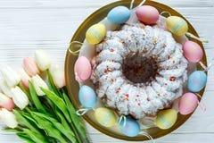 Gelukkige Pasen! Het gouden dienblad met plaat met cake en hand schilderde kleurrijke eieren, tulpen op witte houten lijst Sluit  royalty-vrije stock fotografie