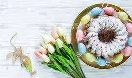 Gelukkige Pasen! Het gouden dienblad met plaat met cake en hand schilderde kleurrijke eieren, tulpen op witte houten lijst Sluit  royalty-vrije stock afbeeldingen