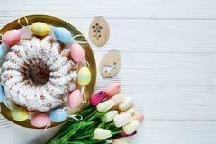 Gelukkige Pasen! Het gouden dienblad met plaat met cake en hand schilderde kleurrijke eieren, tulpen op witte houten lijst Sluit  stock foto