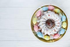 Gelukkige Pasen! Het gouden dienblad met plaat met cake en hand schilderde kleurrijke eieren, tulpen op witte houten lijst Sluit  stock afbeeldingen