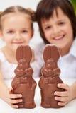 Gelukkige Pasen jonge geitjes met grote chocoladekonijntjes Royalty-vrije Stock Foto's