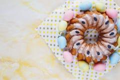 Gelukkige Pasen! Met de hand gemaakte cake op handdoek, eieren, houten konijntjeskonijn op gele marmeren achtergrond Decoratie vo royalty-vrije stock afbeelding