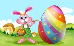 Gelukkige Pasen met konijntje het schilderen ei Stock Fotografie