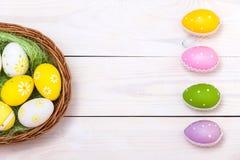 Gelukkige Pasen! Paaseieren in nest op witte houten achtergrond Hoogste mening met exemplaarruimte stock foto