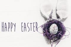 Gelukkige Pasen tekst De kaart van seizoen` s Groeten konijntjesoren en naalden stock foto