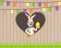 Gelukkige Pasen wenst u konijntje met ei en wortel achter omheining op het gat van de haardvorm stock illustratie