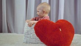 Gelukkige pasgeboren baby die en met hart glimlachen spelen stock videobeelden