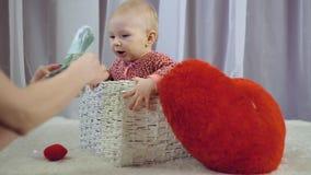 Gelukkige pasgeboren baby die en met hart glimlachen spelen stock video